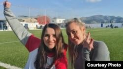Мария Ковалева (сол жақта) әріптесімен бірге футбол алаңында отыр.