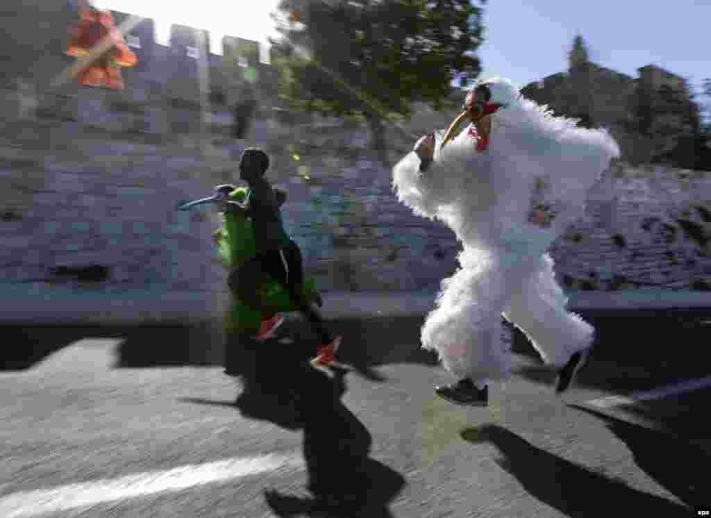 Israeli street performers run along next to a marathon contestant as they pass the Old City walls and the Tower of David complex during the fourth annual Jerusalem Marathon. (AFP/Jim Hollander)