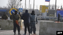 Pro-Russian servicemen man a position at the Chongar checkpoint on March 7, blocking a road into Crimea.