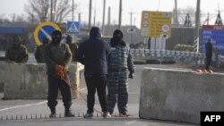 Пророссийские военнослужащие охранют пропускной пункт перед въездом в Крым. 7 марта 2014 года.