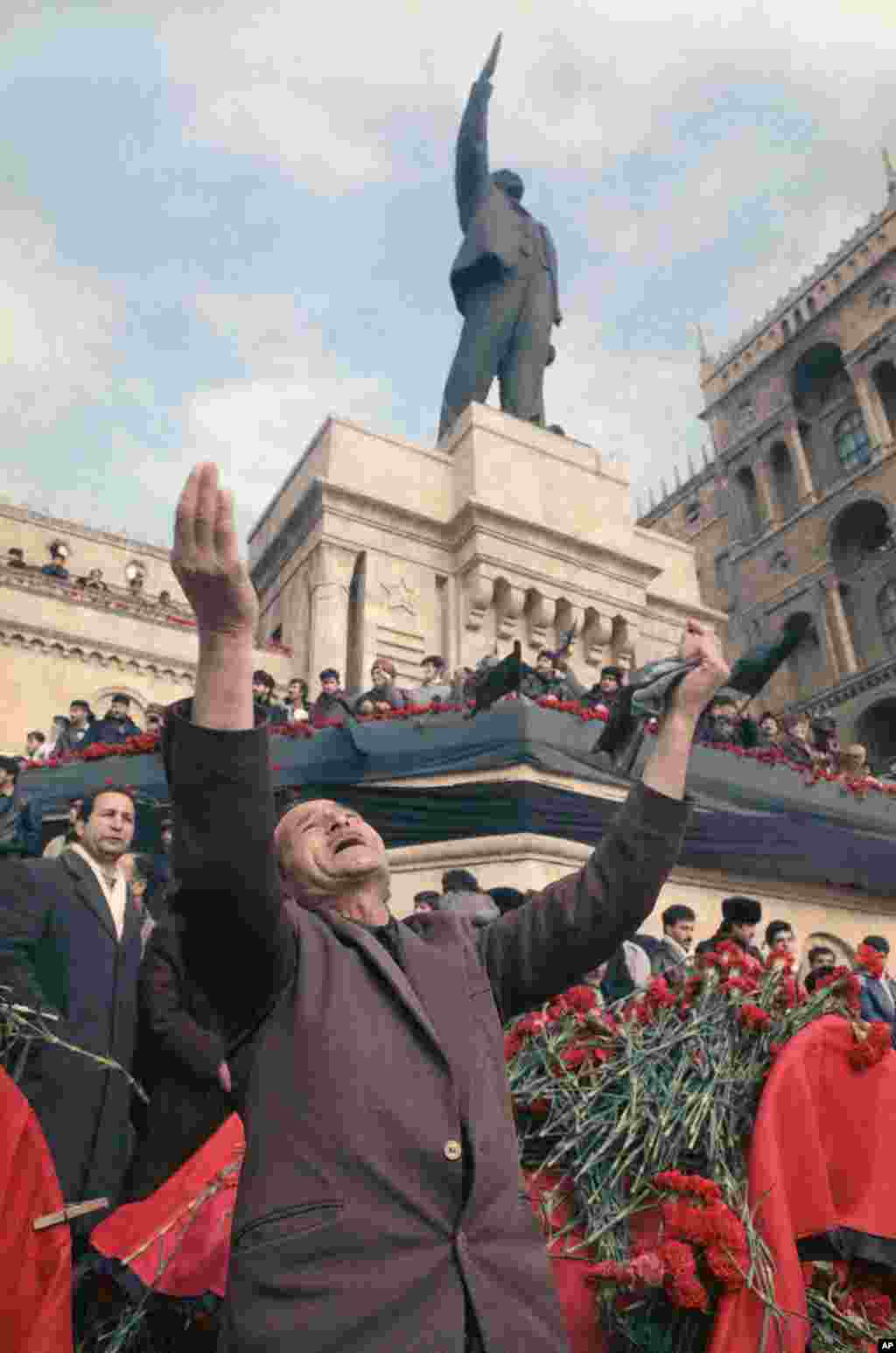 A man lifts his arms in grief under a statue of Lenin during a mass funeral in Baku. The traditional 40-day mourning period for the dead was marked by a national strike across Azerbaijan.