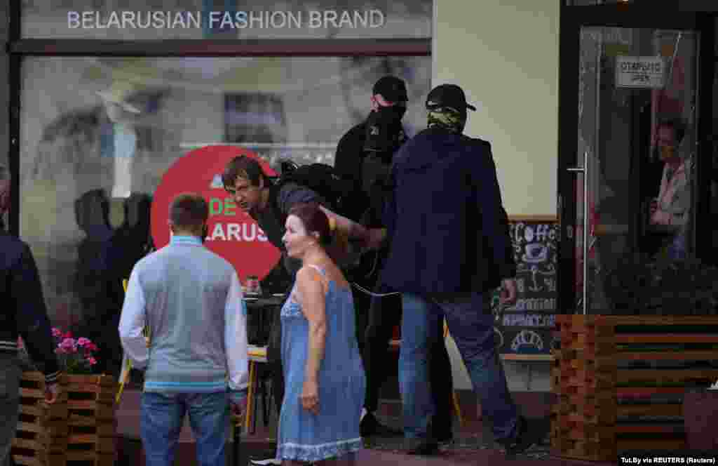 Людзі ў масках пасьля таго, як яны разьбілі шкляныя дзьверы ў кавярні ў раёне Нямігі