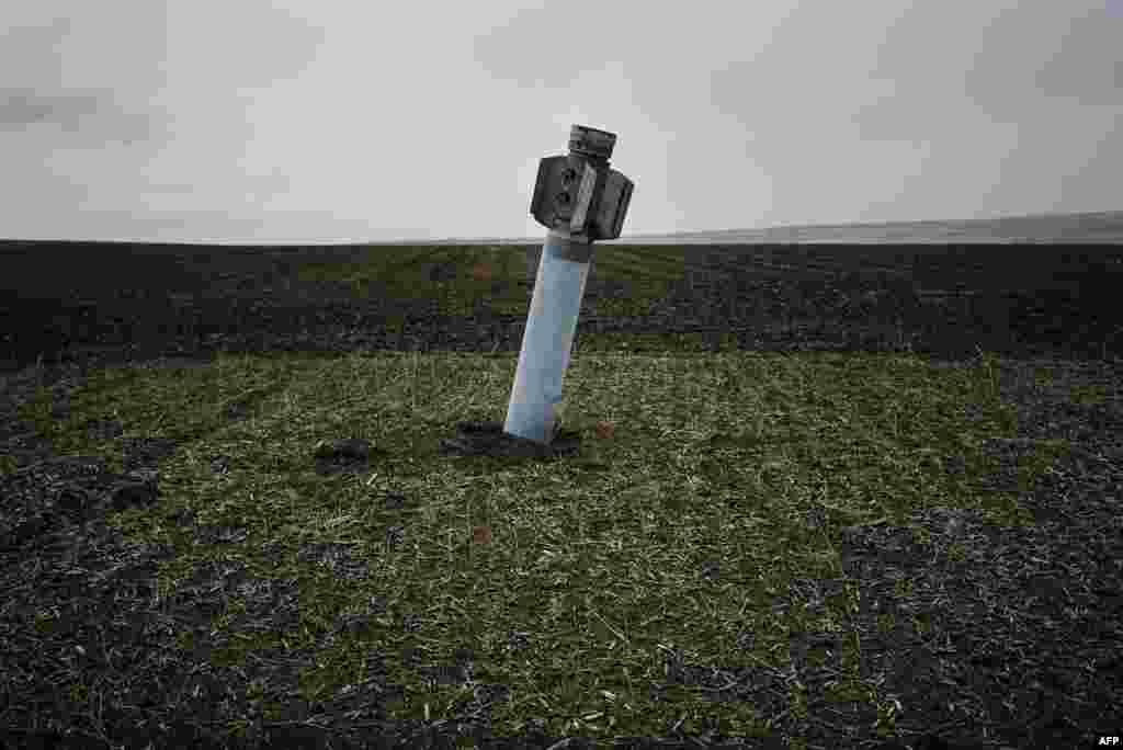 An unexploded rocket stands in a field near the eastern Ukrainian village of Dmitrivka. (AFP/Dimitar Dilkoff)