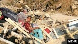Қираған үйінің үстінде отырған бала. Иран, 12 тамыз 2012 жыл.