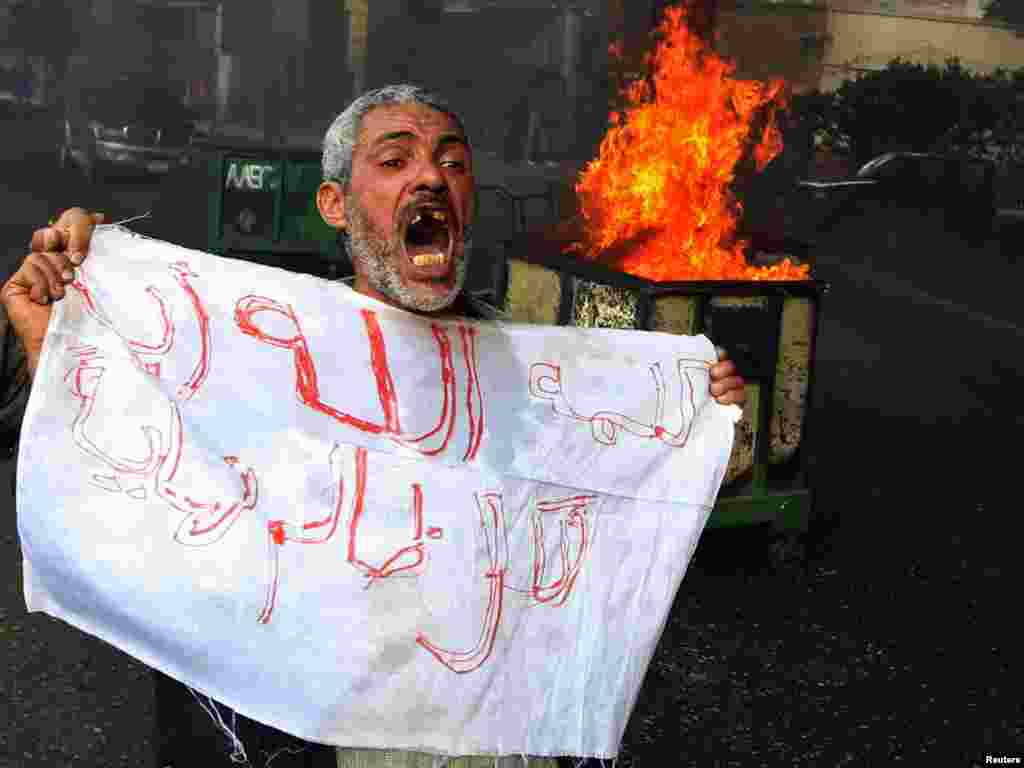 A protester shouts in front of a burning barricade during a demonstration in Cairo on January 28.