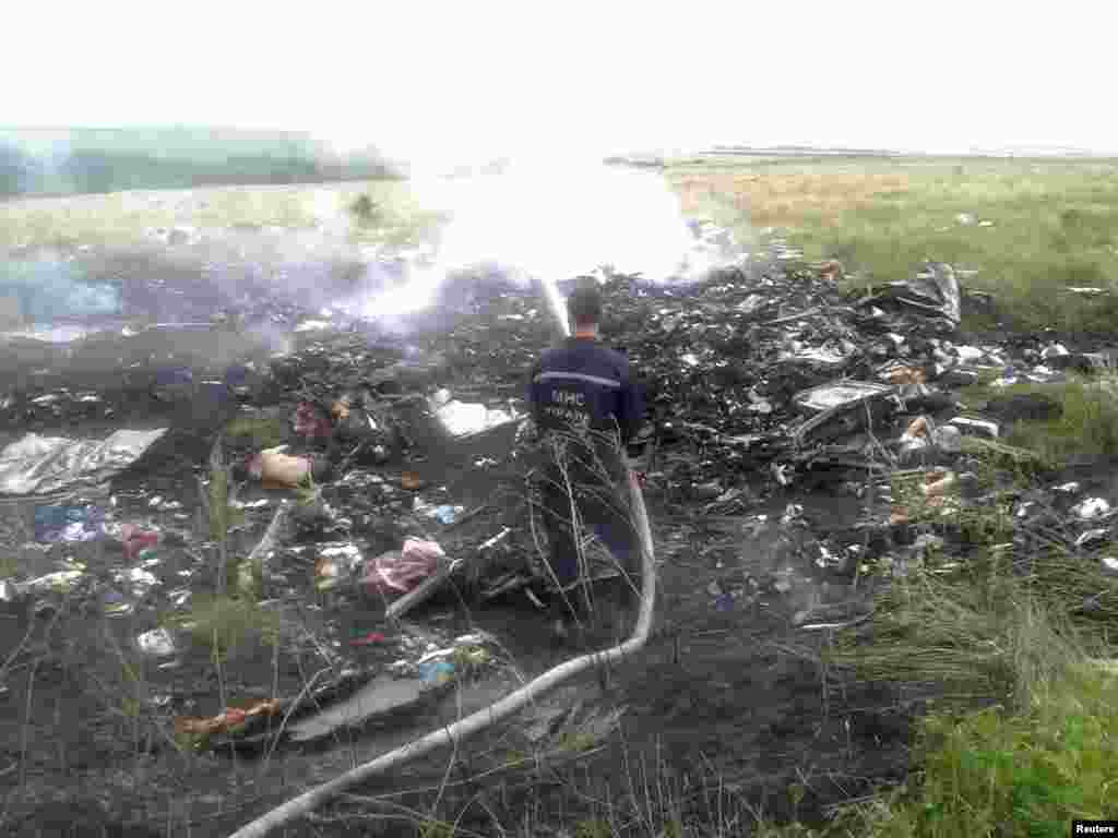 A man hoses down the burning wreckage of the Malaysia Airlines jet.