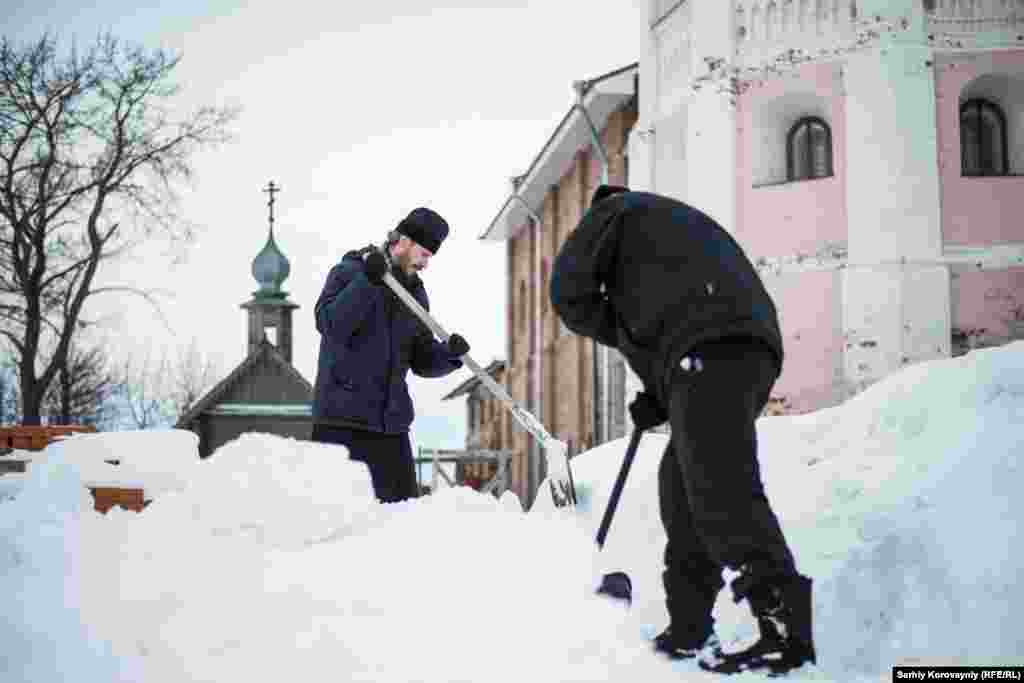 Abbot Dionysius and Kirill, a guest of the monastery, shovel snow. Kirill's life is strongly connected to the monastery. He comes for periods of up to a week, and takes part in religious ceremonies and routine life there.