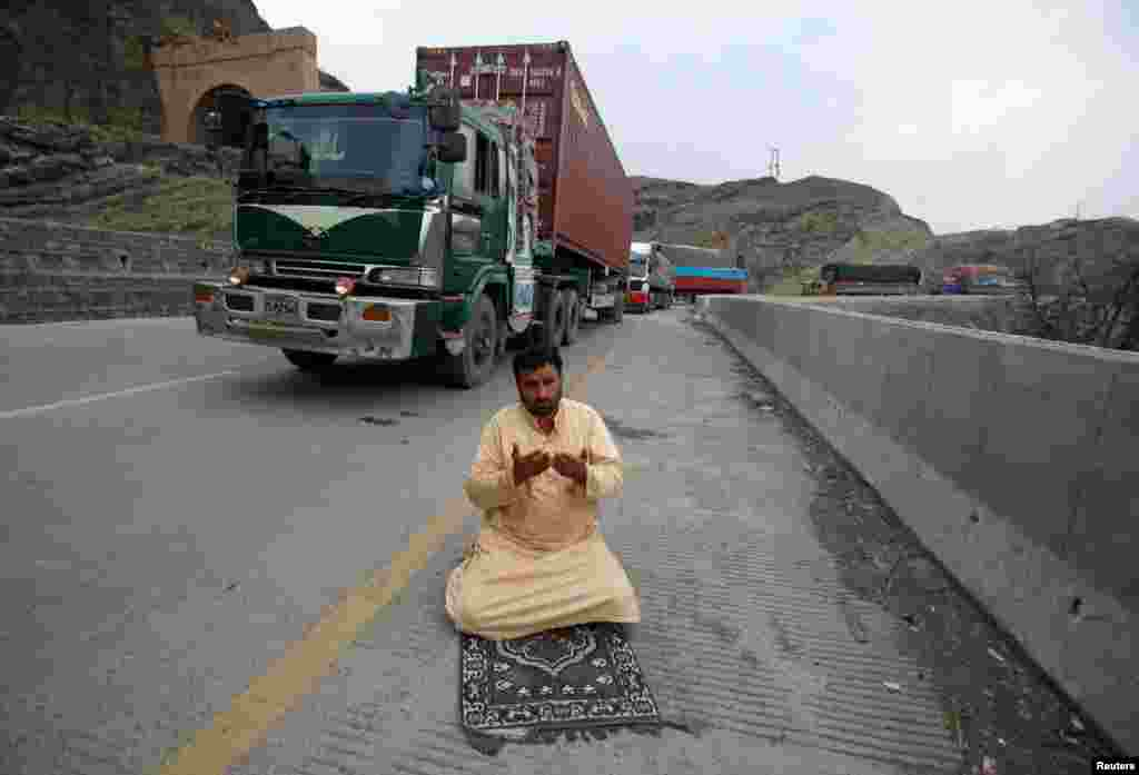 "A truck driver offers afternoon prayers near his supply truck after the opening of the Torkham border crossing to Afghanistan in Landi Kotal, Pakistan. Pakistan ordered the two main border crossings with Afghanistan to be reopened on March 20, calling it a ""goodwill gesture."" The border closures on February 16 had left hundreds of thousands of people stranded at the two major crossings of Torkham and Chaman. (Reuters/Fayaz Aziz)"