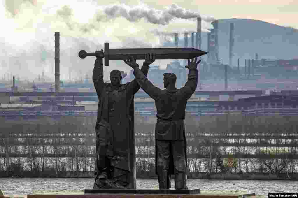 The Rear-Front Memorial in the Russian city of Magnitogorsk. The monument depicts a soldier and a steelworker holding a sword, with the worker facing the vast steel mills that supplied Soviet forces during World War II.