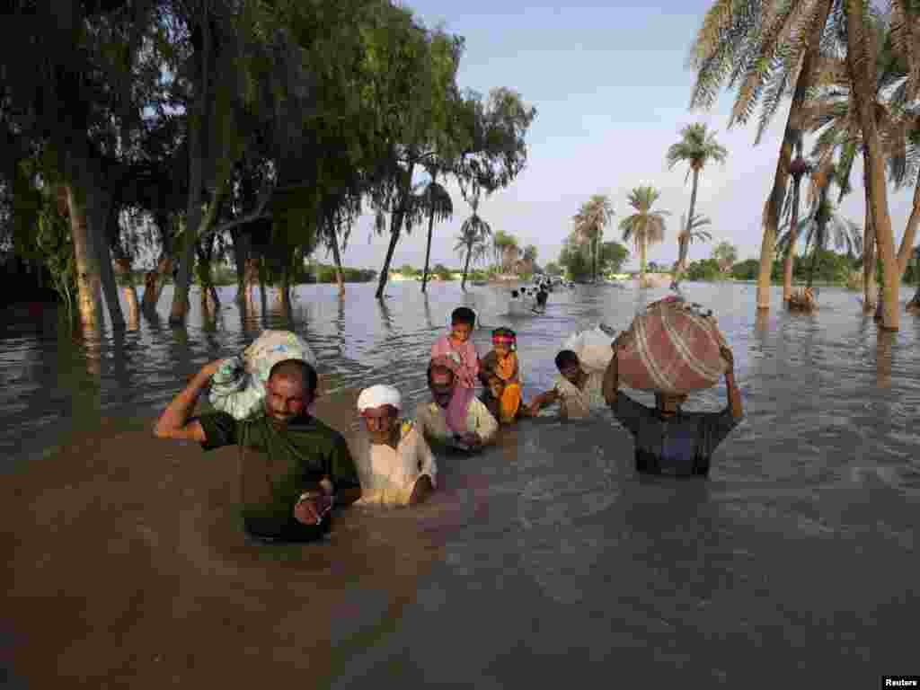 A family wades through floodwaters while evacuating Baseera, a village in Pakistan's Punjab Province, on August 10. The floods, triggered by unusually heavy monsoon rains over the upper Indus River basin that started nearly two weeks ago, have plowed a swathe of destruction more than 1,000 kilometers long from northern Pakistan to the south.Photo by Adrees Latif for Reuters