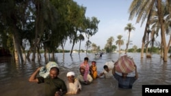 A family wades through flood waters while evacuating Baseera, a village in Punjab Province, where the Kalabagh Dam would be located.