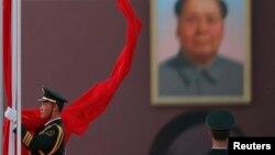 Қытайдың бұрынғы басшысы Мао Цзедунның үлкен суреті ілінген Тяньаньмэнь алаңында мемлекеттік туды көтеріп жатқан адам. Пекин, 4 наурыз 2013 жыл. (Көрнекі сурет)