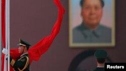 Афіцэр уздымае кітайскі сьцяг на плошчы Цяньаньмэнь, 4 сакавіка 2013 году. На фоне - партрэт - Мао Цзэдун