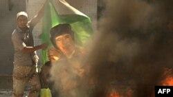 Ливийский повстанец жжет плакат с портретом Муамара Каддафи
