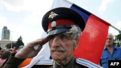 "A veteran Cossack salutes in front of the Russian flag as pro-Russian militants take a military oath of allegiance to the so-called ""Donetsk People's Republic"" on June 22."