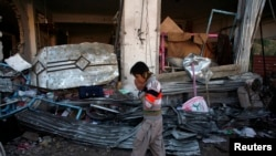 A boy reacts as he walks past the site of a bomb attack in a Shi'ite Muslim area in Quetta that killed more than 80 people.