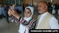 Afghan teenager Fatema Qaderyan takes a photograph with her father at Herat International Airport before heading to the United States last month for a robotics competition.