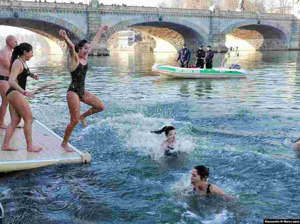 "Italy, January 28: Young ""Polar Bears"" dive into the icy water of the Po River in Turin. Three days after this photo was taken, two Chinese tourists in Rome tested positive for the coronavirus. The disease has killed 6,077 people in Italy as of March 23 -- the largest death toll of any country during the pandemic."