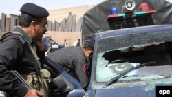Security officers inspect a police vehicle after four police officers were killed in Quetta.