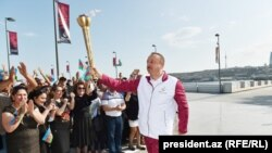 Ilham Aliyev holds the torch carrying the European Games' flame
