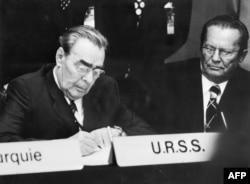Леонид Брежнев подписывает Хельсинкские соглашения под пристальным взглядом главы коммунистической Югославии Иосипа Броз Тито, 1 августа 1975