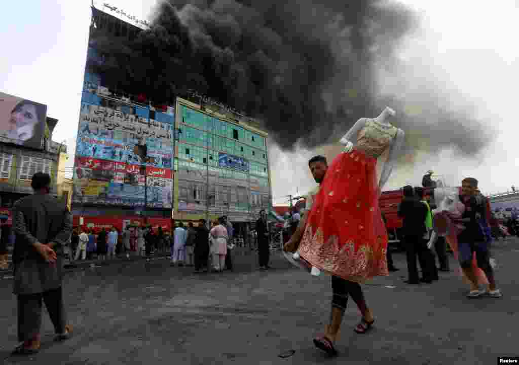 An Afghan shopkeeper carries a mannequin after a fire broke out at a shopping mall in Kabul. (Reuters/Omar Sobhani)