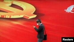 Мужчина в маске идет на фоне эмблемы Компартии Китая. Пекин, 23 апреля 2013 года.
