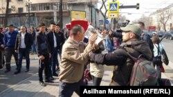 Неизвестный пытается закрыть газетой объектив камеры съемочной группы Азаттыка. Алматы, 22 марта 2019 года.
