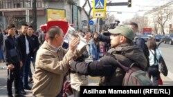 Неизвестный мужчина закрывает объектив камеры журналистов Азаттыка, освещающих задержания на акции протеста в Алматы. 22 марта 2019 года.