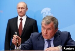 President Vladimir Putin (back) ruled that state-controlled Rosneft, headed by Igor Sechin (right), could participate in the Bashneft privatization.