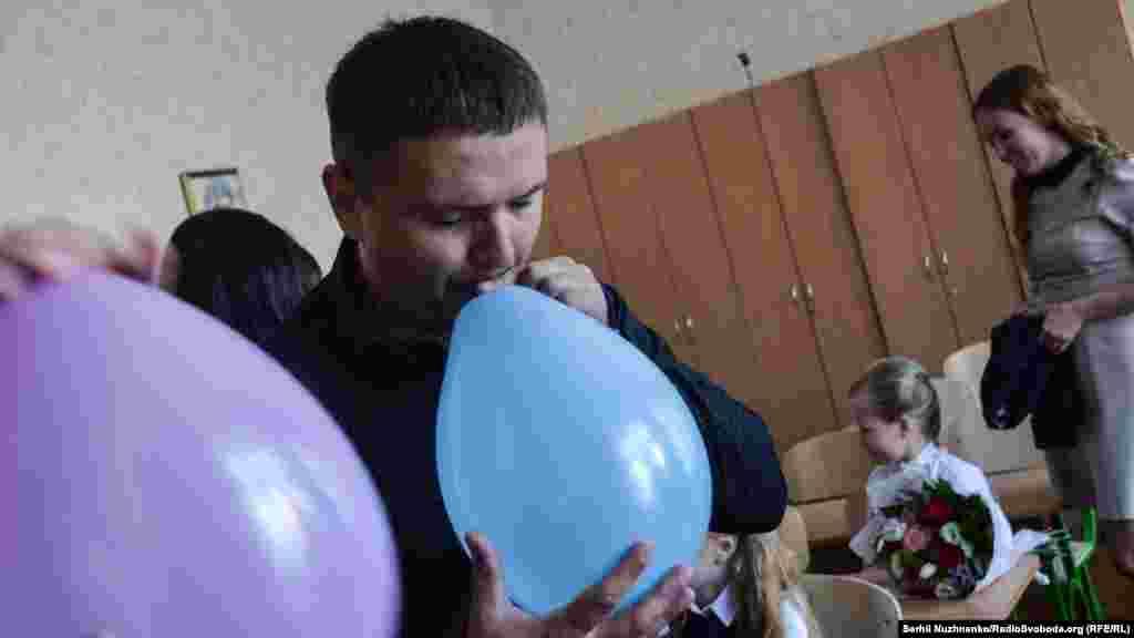 Тато Даші надуває кульки й допомагає прикрасити клас для першого уроку. Він працює в Києві й відпросився з роботи для того, щоб потрапити на «Перший дзвінок» до доньки