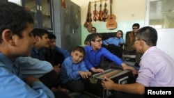Visually impaired Afghan students play musical instruments during a music lesson at the Kabul Blind School.