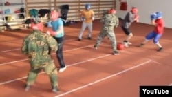 """A screen grab from a YouTube video of young men playing """"Russian football,"""" which is billed as a hybrid sport between football/rugby and boxing."""