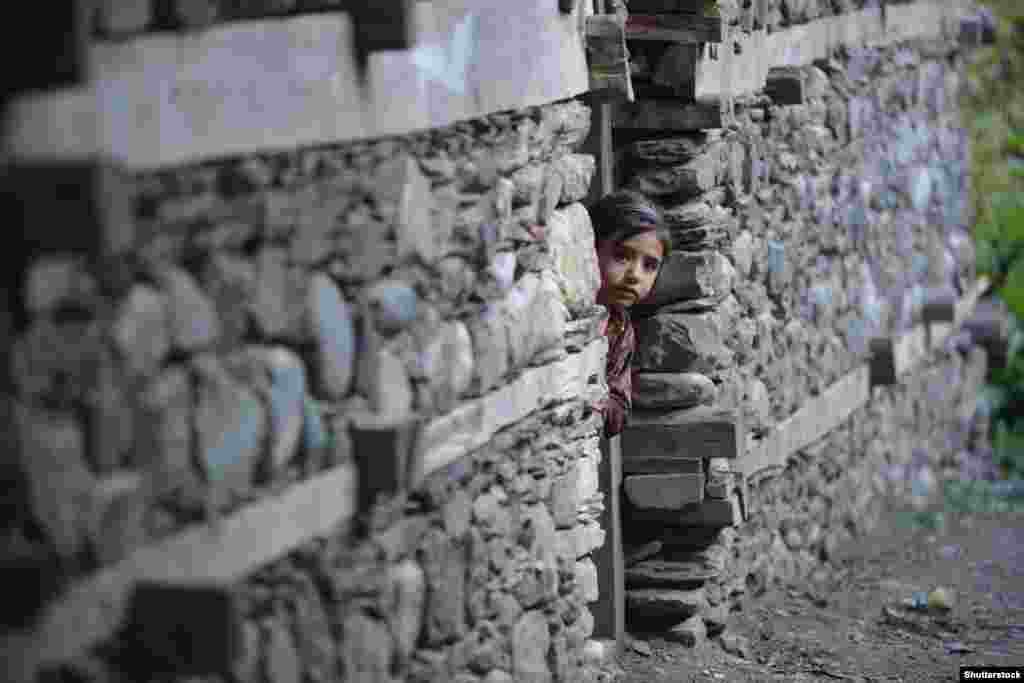 """A little Kalash girl peers out of her house. In 2013, the Pakistani Taliban vowed the Kalash would be """"eliminated, along with their protectors, the Western agents, if they do not embrace Islam."""" (Photo by Shutterstock)."""