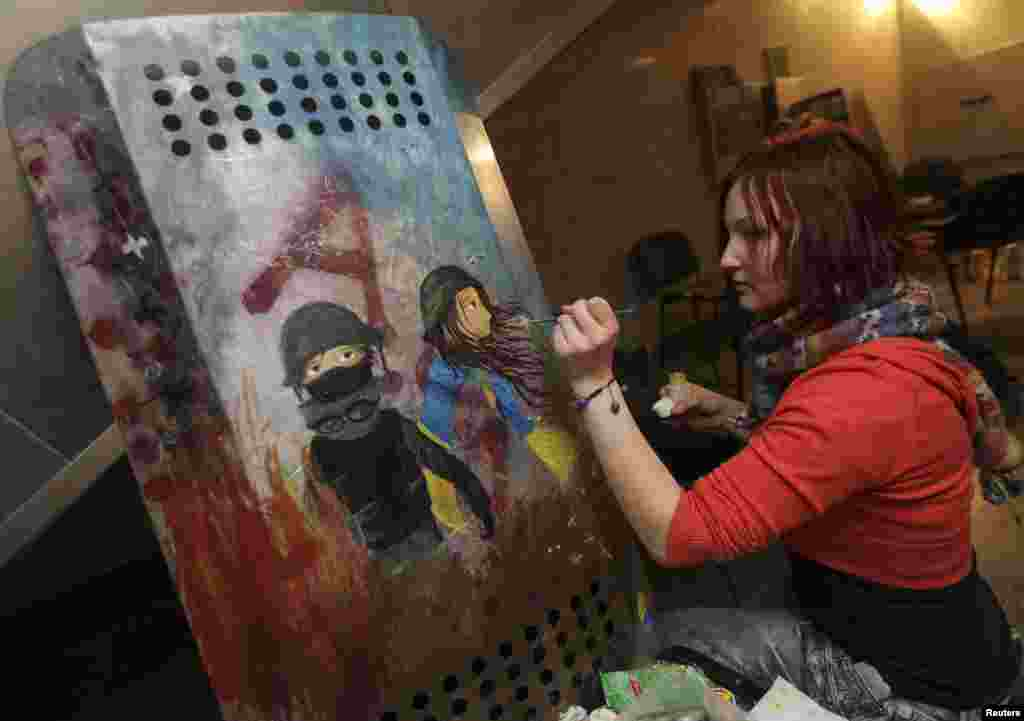 An artist decorates the shield of an antigovernment protester in Kyiv.