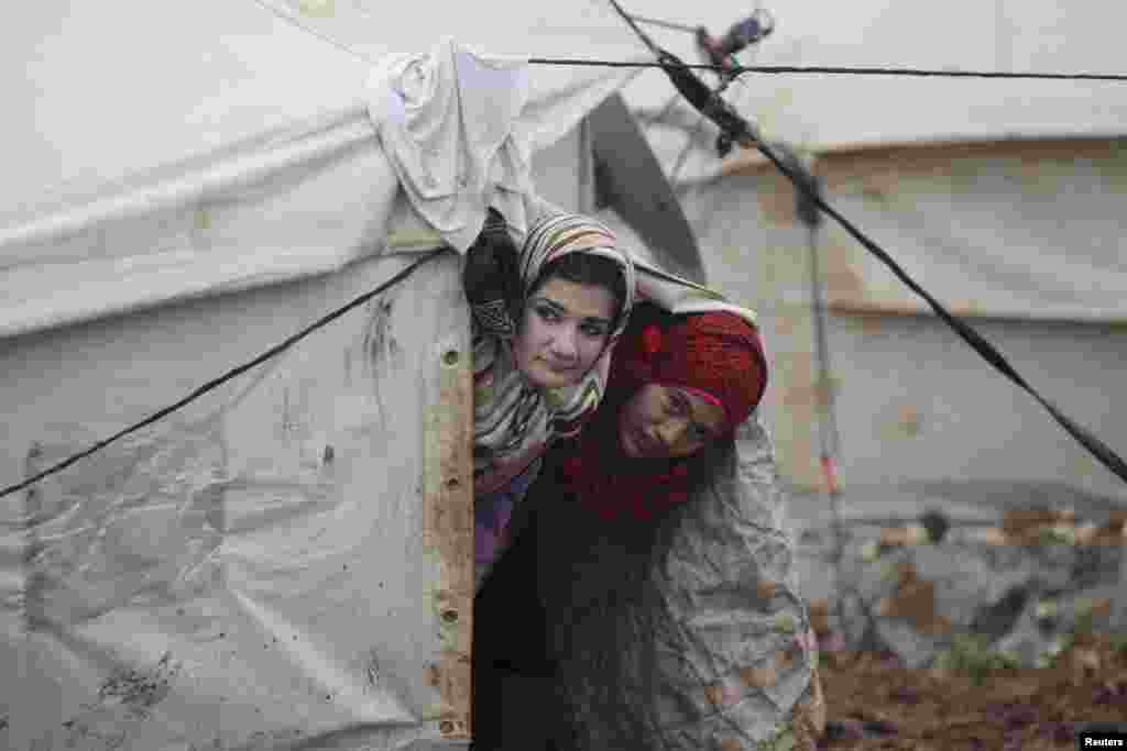 Internally displaced girls look out from their tent inside the Al-Karameh refugee camp beside the Syrian-Turkish border in Syria's northern Idlib countryside. (Reuters/Khalil Ashawi)