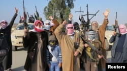 Tribal fighters gesture after deploying themselves on the streets of Ramadi on January 6.