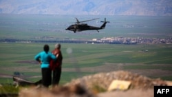 A medical helicopter from the U.S.-led coalition flies over the site of Turkish air strikes near the northeastern Syrian Kurdish town of Derik last month.