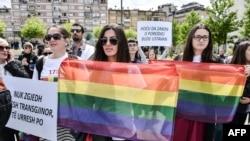 Активисты ЛГБТ-сообщества держат в руках радужные флаги во время во время акции в честь первого гей-парада на главной площади в Приштине. Косово, 17 мая 2016 года.