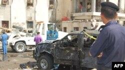 شرطي ينظر الى حطام سيارة في موقع الانفجار بالبصرة