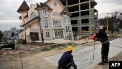 Строители прокладывают дорогу рядом с разрушающимся из-за сползания грунта домом.