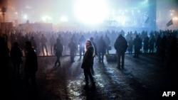 Ուկրաինա - Մարդիկ լրատվական հաղորդում են դիտում Կիևի Անկախության հրապարակում՝ Եվրոմայդանում տեղադրված մեծ էկրանին, 4-ը մարտի, 2014թ․ Ukraine -- A woman looks on as people watch news on a large TV screen at the Independence square in central Kyiv, March 4, 2014