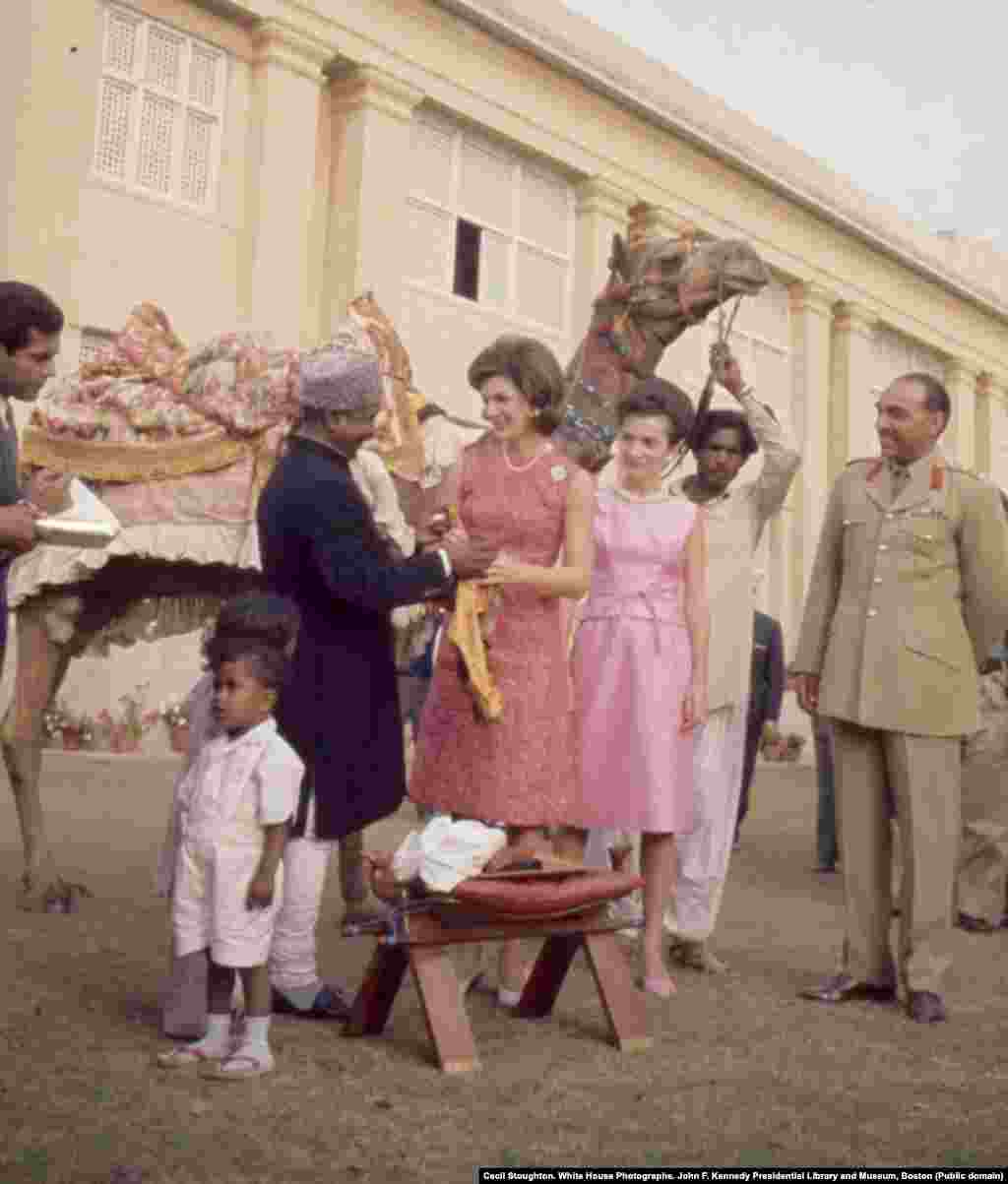 "First lady Jacqueline Kennedy and her sister, Lee Radziwill, meet camel driver Bashir Ahmad. Ahmad had formed a friendship with U.S. Vice President Lyndon Johnson the year before after Johnson stopped to shake the camel driver's hand on his own trip to Pakistan. After Johnson casually invited Bashir to ""come see me sometime,"" Bashir accepted the invitation. He became a media spectacle after he traveled to the United States to meet with Johnson and the Kennedys."