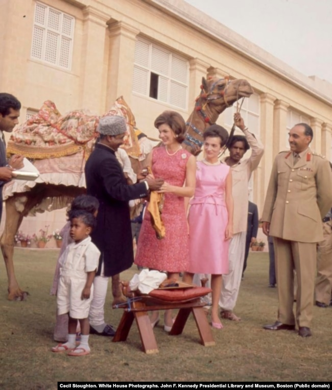 """First lady Jacqueline Kennedy and her sister, Lee Radziwill, meet camel driver Bashir Ahmad. Ahmad had formed a friendship with U.S. Vice President Lyndon Johnson the year before after Johnson stopped to shake the camel driver's hand on his own trip to Pakistan. After Johnson casually invited Bashir to """"come see me sometime,"""" Bashir accepted the invitation. He became a media spectacle after he traveled to the United States to meet with Johnson and the Kennedys."""