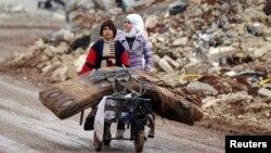 خواهر برادر نوجوان سوری باقیماندههای محل سکونت خود در حلب را به مکانی دیگر انتقال میدهند. دوم ژانویه ۲۰۱۷.