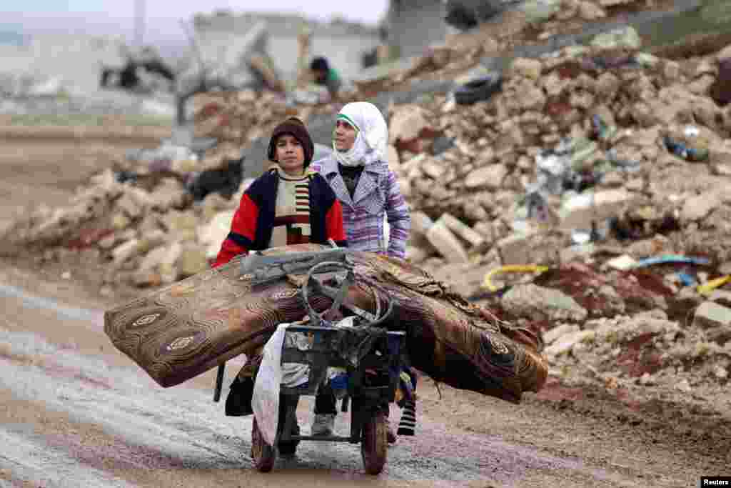 Samah, 11, and her brother Ibrahim transport salvaged belongings from their damaged house in the village of Doudyan in northern Aleppo Governorate, Syria. (Reuters/Khalil Ashawi)