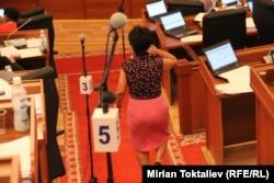 Женщина проходит мимо депутатских столов в парламенте. Бишкек, 27 июня 2012 года.