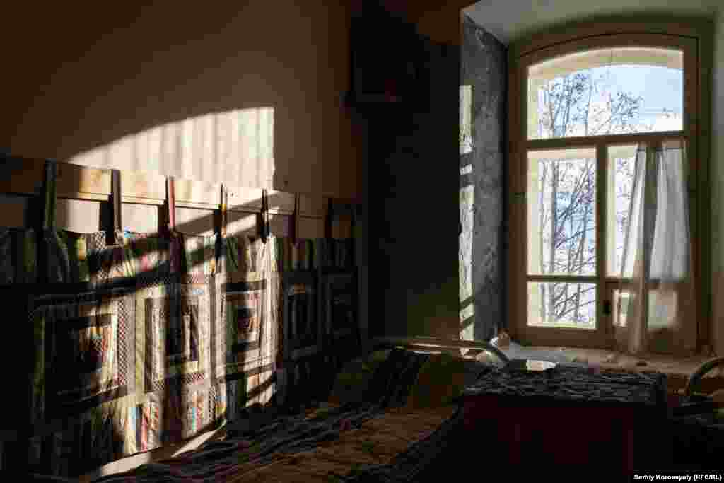 Sunlight streams through a monastery bedroom window.