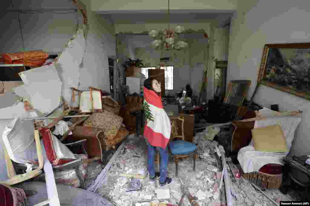 Farah Mahmoud, wrapped in Lebanese national flag, checks her parents destroyed apartment after Tuesday's explosion in the seaport of Beirut, Lebanon, Thursday, Aug. 6, 2020.