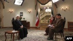 Iranian President Hassan Rohani (left) during an interview broadcast live on state television in Tehran on February 5.